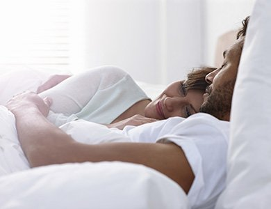 Man and woman sleeping soundly thanks to snoring solutions in Orange California