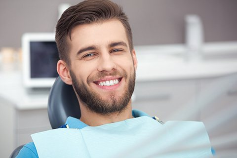 A young man sitting in the dentist's chair waiting for his regular checkup in Orange