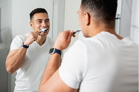 A man standing in front of his bathroom mirror brushing his teeth in Orange