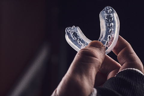 An up-close image of a person holding a customized mouthguard in Orange