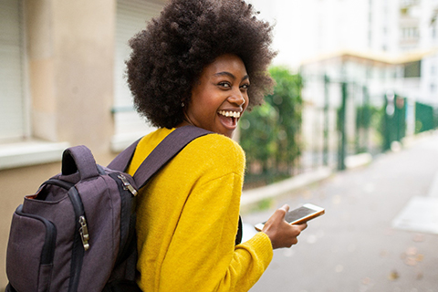 A young woman wearing a yellow sweater and purple backpack holding her phone and smiling in Orange